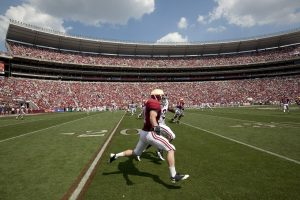 NCAA Football Player running with support of Booster Club Stadium funding