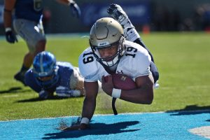 NCAA College Football Player crossing goal line with support of booster club