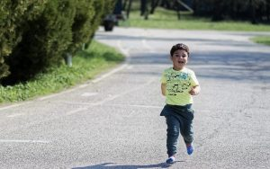Little kid running with booster club printed T-Shirt on