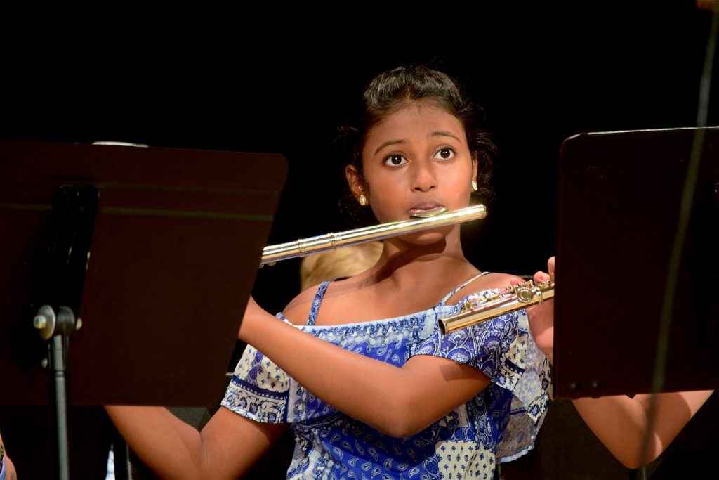 Student playing flute in orchestra