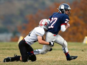 Football team player getting tackled in game