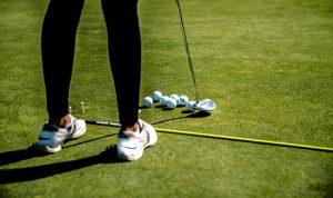 School golf team member practicing putting